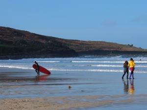 A Longboarder finishing a sunny winter surf